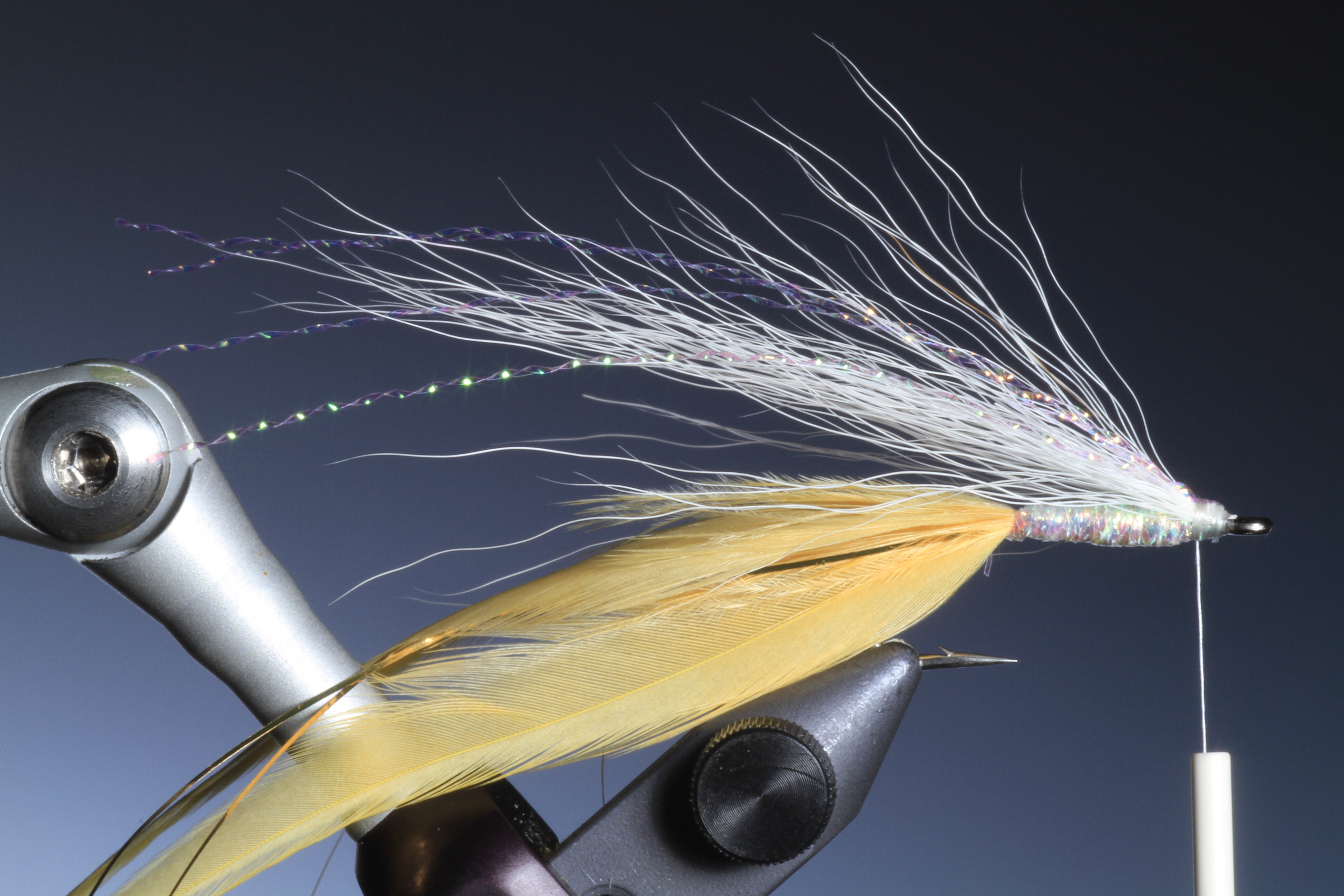 5. tie in a bunch of white buck tail and a few strands of crystal hair for the wing.
